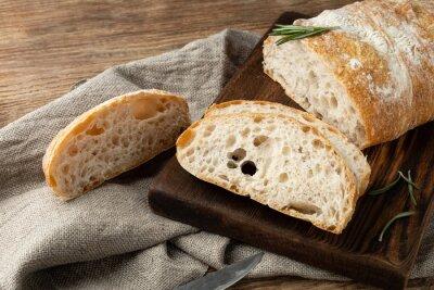 Fototapeta Delicious homemade sliced Italian ciabatta bread on a wooden cutting board. Close-up.