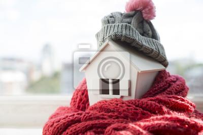 Fototapeta dom w zimie - koncepcja systemu grzewczego i zimna śnieżna pogoda z modelem domu w czapce z dzianiny