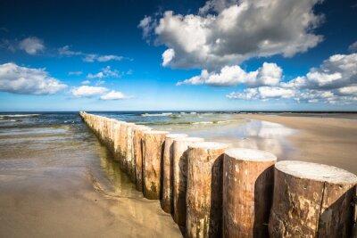 Fototapeta Drewniane falochrony na piaszczystej plaży w Łebie późnym popołudniem, Bałtyk