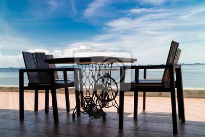 Fototapeta Drewniane Krzesła I Stolik Na Tarasie Restauracji Morskiej Przeciwko