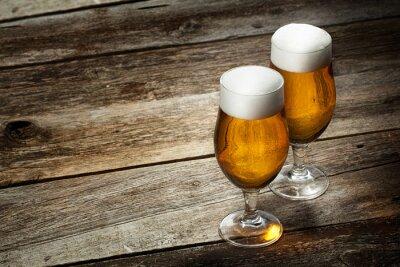 Fototapeta Dwie szklanki do piwa na tle drewna z copyspace