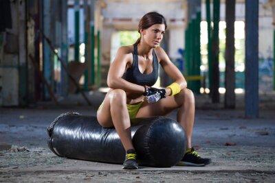 Fototapeta Dziewczyna worek bokserski siedzenia na