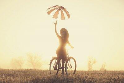 Fototapeta Dziewczyna z parasolem na rowerze na wsi w czasie wschodu słońca