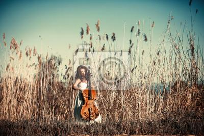 Fototapeta Dziewczyna z wiolonczela w wysokiej trawie
