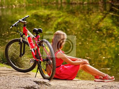 03816b9d Fototapeta: Dziewczynka ma na sobie czerwony sukienka przejażdżki rowerem
