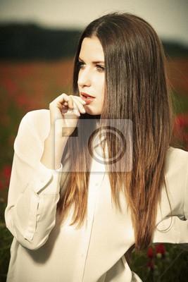 Fototapeta Dziewczynka w dzikich czerwonych kwiatów maku w okresie letnim