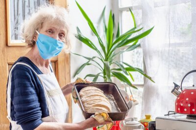 Fototapeta Elderly woman in protective mask bakes bread at home in the kitchen. Quarantine coronavirus covid-19. Good housewife grandmother with homemade bread on a baking tray. Stay at home. Homemade food. Cook