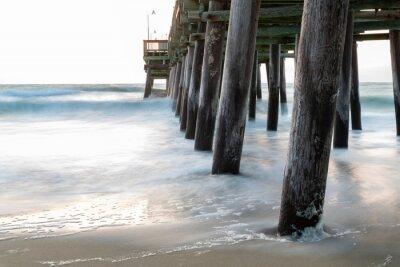 Fototapeta Fale plusk wzdłuż molo Sandbridge Fishing w Sandbridge Virginia, Virginia Beach podczas wschodu słońca. Pastelowe kolory i marzycielski wygląd