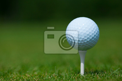 Fototapeta golf ball on a white tee with a green grass in background