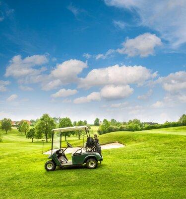 Fototapeta Golf cart on a golf course. Green field and cloudy blue sky