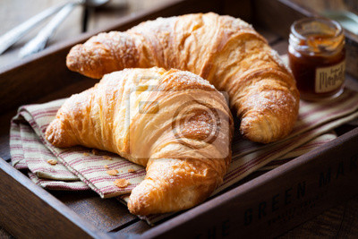 Fototapeta Good morning concept - Freshly baked croissants on a tray with a small jar of jam for breakfast