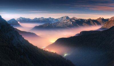 Fototapeta Góry w mgle przy piękną nocą w jesieni w dolomitach, Włochy. Krajobraz z alpejską górską doliną, niskie chmury, las, kolorowe niebo z gwiazdami, iluminacja miasta o zmierzchu. Antenowy. Passo Giau