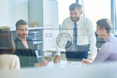 Fototapeta Grupa ludzi biznesu pomyślne omawianie pracy podczas spotkania w biurze, koncentrują się na uśmiecha się Brodaty mężczyzna mówi do pracowników strzał zza szklane drzwi