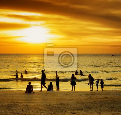 Fototapeta Grupa ludzi na zachodzie słońca plaży