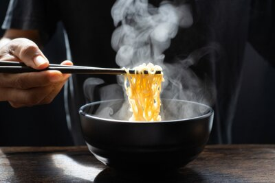 Fototapeta Hand uses chopsticks to pickup tasty noodles with steam and smoke in bowl on wooden background, selective focus. Asian meal on a table, hot food and junk food concept