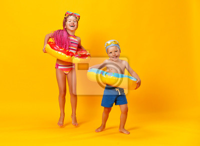 Fototapeta happy children girl and boy in swimsuit with swimming ring donut on colored yellow background.