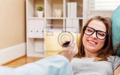 Fototapeta Happy młoda kobieta oglądania telewizji w salonie