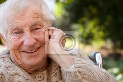 Fototapeta Happy starszy kobieta na wózku inwalidzkim z uśmiechem na zewnątrz