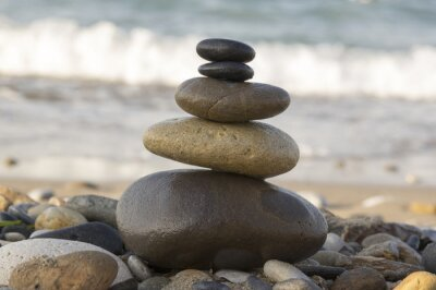Fototapeta Harmonia i równowaga, zen cairn na żwirowej plaży, fale morskie na tle