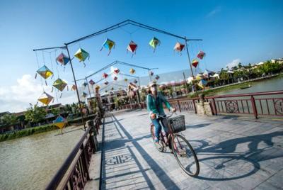 Fototapeta Hoi An Wietnam 24 października 2012: Niezidentyfikowany rowerzysta kolarz minięciu mostu i dekoracji lampy ponad Hoai River w starożytnego miasta Hoi An Światowego Dziedzictwa UNESCO w Quang Nam Wietn