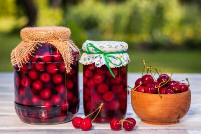 Fototapeta Homemade cherry fruit compote in jar and harvested red cherries in bowl
