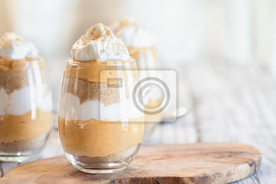 Fototapeta Homemade pumpkin trifle dessert made from pumpkin puree, cream cheese, cookie crumbs and whipped cream. Extreme selective focus with blurred background.