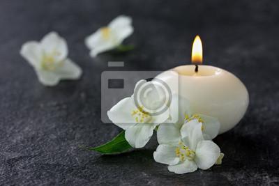 Jasmine kwiaty i palące się świece na spa na czarno