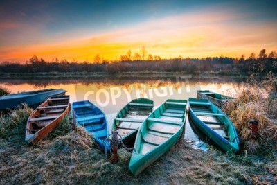 Fototapeta Jezioro, rzeka i wioślarstwo łodzi na piękny wschód słońca w jesiennym poranku. Stare drewniane łodzie i matowe trawy.