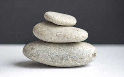 Fototapeta Kamienie piramidy na bia? Ym stole i czarnym tle, zbalansowane piramidy kamieni do medytacji i odpoczynku