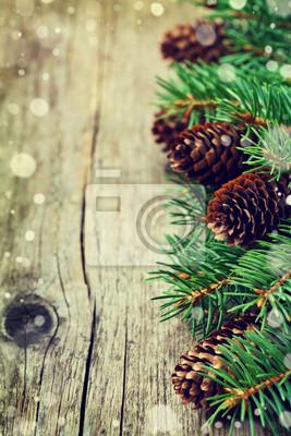 Kartka świąteczna z jodły i szyszka na drewnianych tle, efekt śniegu, kopia przestrzeń dla tekstu, rocznik tonowanie