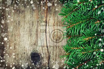 Kartka świąteczna z jodły na drewnianych tle, efekt śniegu, kopia przestrzeń dla tekstu, rocznik tonowanie