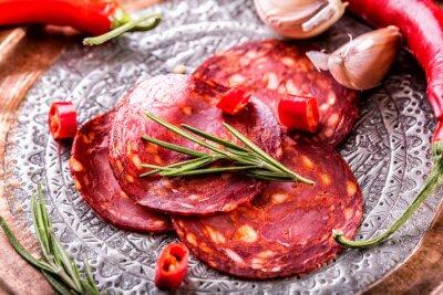Fototapeta Kiełbasy chorizo. Hiszpańska tradycyjna kiełbasa chorizo, świeżymi ziołami, czosnkiem, pieprzem i papryką chili. Tradycyjna kuchnia.