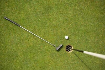 Fototapeta Klub golfowy i piłka golfowa na putting green obok flagi