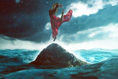 Fototapeta Kobieta tańczy na skale w morzu