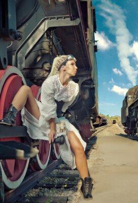 Fototapeta Kobieta w zabytkowe Sukienka siedzi na koła lokomotywy.