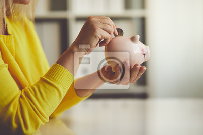 Fototapeta Kobieta wkłada monetę do skarbonki