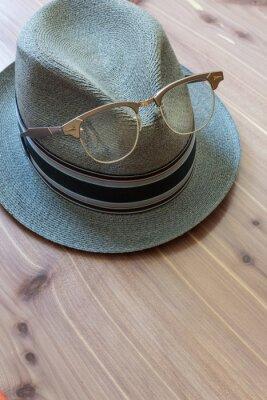 Fototapeta Koncepcja rocznika hipster retro kapelusz fedora, okulary oprawione w metalową róg wznosi się z przodu, neutralne tło drewna, kopia przestrzeń, aspekt pionowy