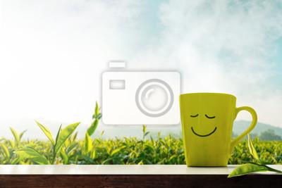 Fototapeta Koncepcja szczęśliwy i relaks. Filiżanka Gorąca herbata z Smiley twarzą na stole przed Zielonej Herbaty Plantaion Gospodarstwem, góra z mgłą jako tło
