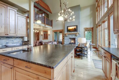 Fototapeta Large luxury wooden kitchen interior with light wood hardwood floor and dark granite slab on island with huge windows.
