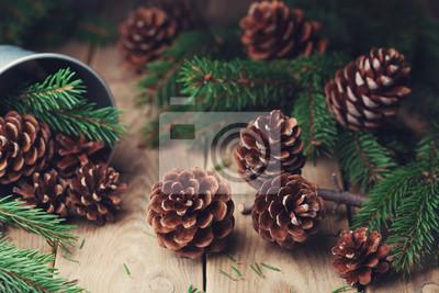 Lasowy skład z sosnowymi rożkami i jedlinowa gałąź na nieociosanym drewnianym stole. Kartka świąteczna.