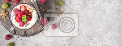 Fototapeta Letni zdrowy deser z malinami i jogurtem na desce do krojenia. Format baneru