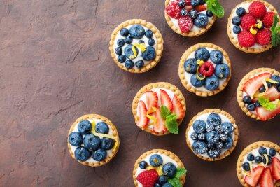 Fototapeta Letnie tartlets lub ciasto z twarogiem i mieszanych jagód widok z góry. Smaczne desery cukiernicze.