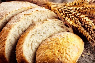 Fototapeta Loaf sliced white bread with ears wheat