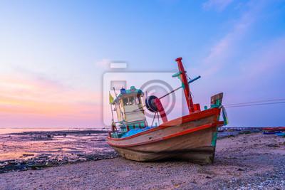 Fototapeta łódź rybacka na brzegu o zachodzie słońca