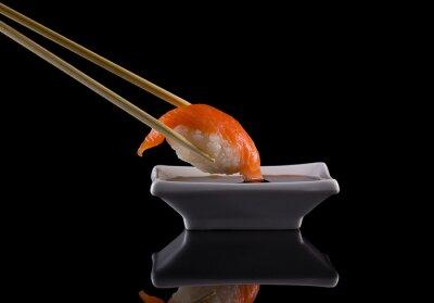 Fototapeta Łosoś sushi nigiri z pałeczkami z sosem sojowym na czarnym tle