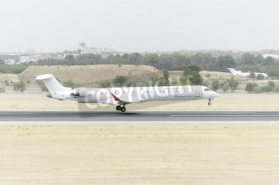 Fototapeta MADRID, Hiszpania - 08 sierpnia 2015: Canadair CRJ Samoloty -Bombardier-900-, z -Air Nostrum- linii lotniczej, jest lądowanie na lotnisku Barajas -Adolfo Suarez-, 8 sierpnia 2015 r.