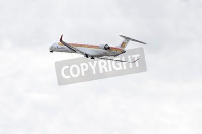 Fototapeta MADRID, Hiszpania - 14 czerwca 2015: Samoloty Canadair CRJ--Bombardier 1000-, z -Air Nostrum- linii lotniczych, startuje z lotniska Madryt-Barajas -Adolfo Suarez-, w dniu 14 czerwca 2015 r.