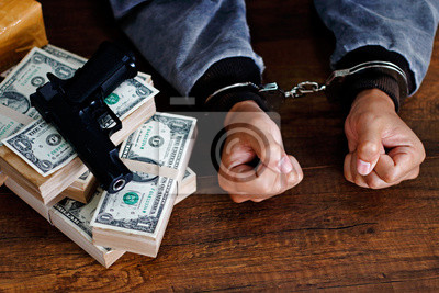 Fototapeta Man in Handcuffs with Drugs, money and gun on wooden table