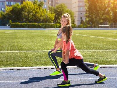 Fototapeta Matki i córki niewiele robią ćwiczenia na stadionie. On