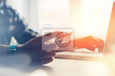 Fototapeta Mężczyzna posiadania karty kredytowej i przy użyciu komputera przenośnego. płatności online (zamierzone słońca blask i obiektywu flary)